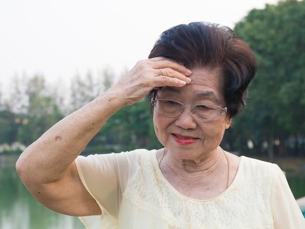 La anciana asiática llevaba unas gafas. no se sentía cómoda con los dolores de cabeza