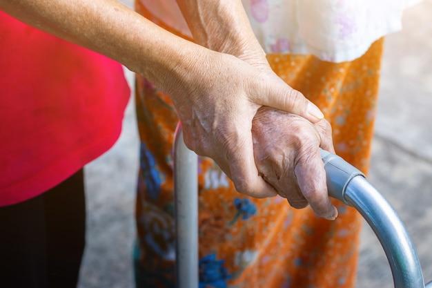 Anciana asiática de pie con la mano en un andador con la mano de la hija