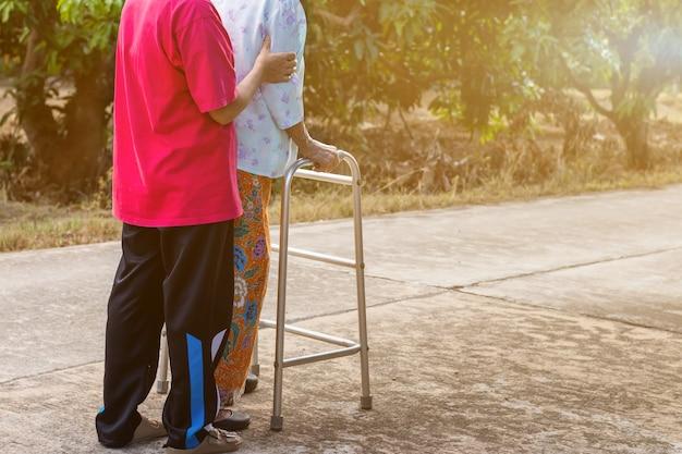 Anciana asiática de pie con las manos en un andador con la mano de la hija