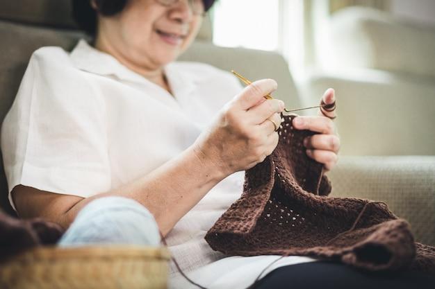 Anciana asiática tejer crochet