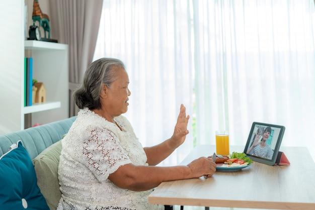 Anciana asiática virtual happy hour reunión y comer comida en línea junto con su hija