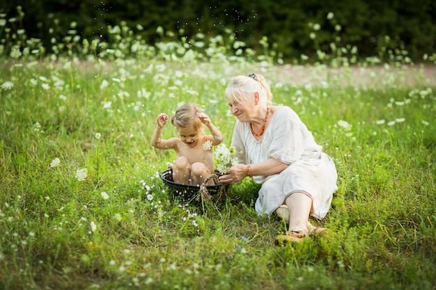 Anciana, baño, niña, en, un, palangana, al aire libre, en, verano, día, alrededor, flores