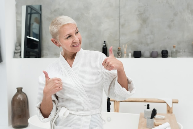 Anciana en bata de baño sonriendo y dando pulgares arriba
