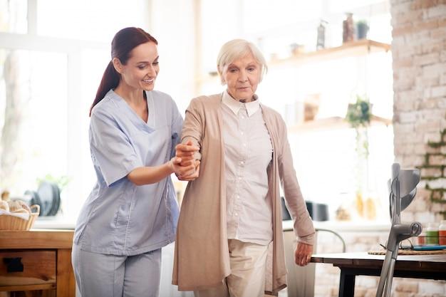 Anciana caminando después de la cirugía con la ayuda de una enfermera