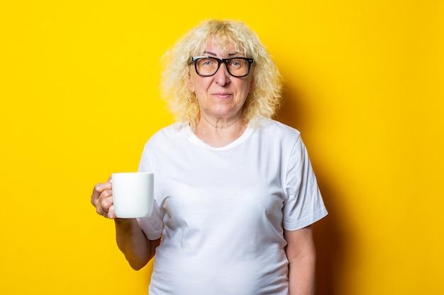 Anciana con camiseta blanca y gafas sostiene una taza de té en una pared amarilla.