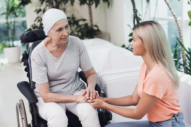 Anciana con cáncer junto a ella sienta a su hija.
