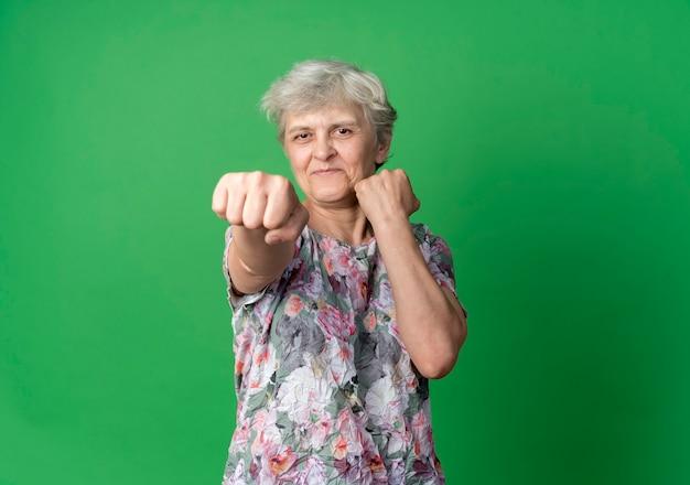 Anciana complacida mantiene los puños listos para perforar aislado en la pared verde