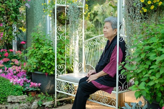 Anciana descansando en el jardín de flores