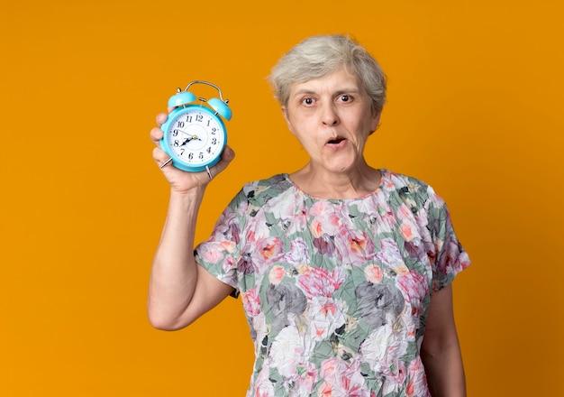 Anciana emocionada sostiene el despertador aislado en la pared naranja