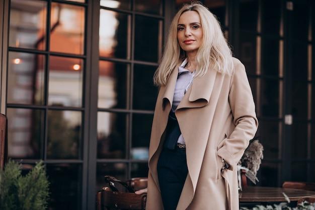 Anciana empresaria en un abrigo fuera del café