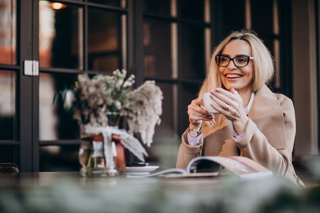 Anciana empresaria en un abrigo sentado afuera de un café y leyendo una revista