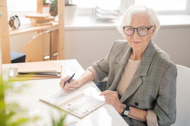 Anciana empresaria con cabello blanco anotar el plan de jornada laboral en el cuaderno por escritorio frente a la cámara