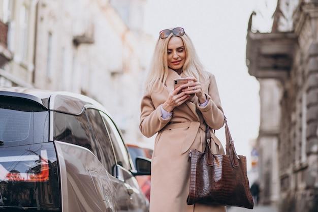Anciana empresaria hablando por teléfono junto a su auto eléctrico