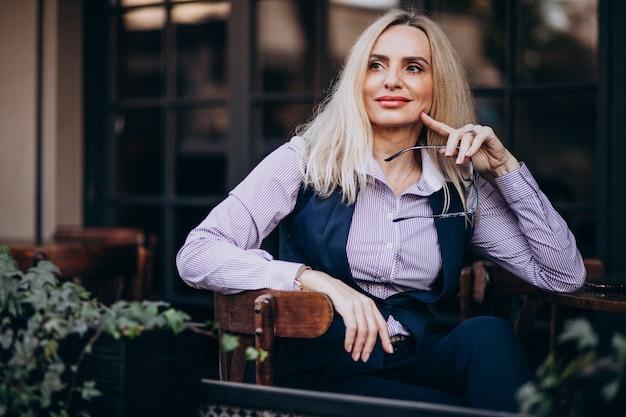 Anciana empresaria sentado afuera del café
