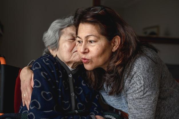 Anciana enferma en silla de ruedas junto a su hija sonriente. tercera edad, concepto de atención domiciliaria.
