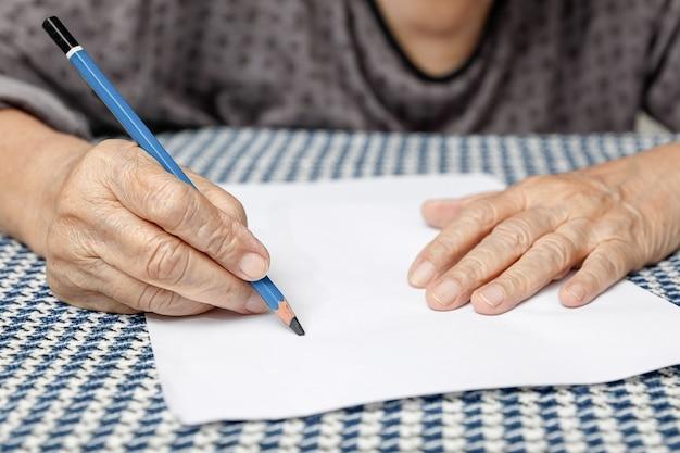 Anciana escribiendo en papel en blanco