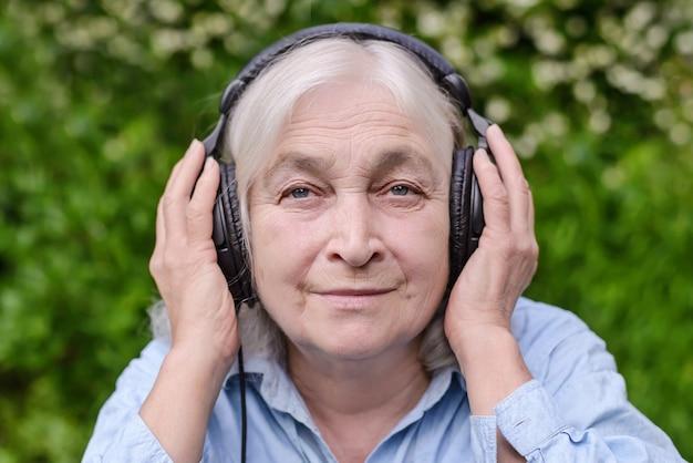 Anciana escuchando música con auriculares