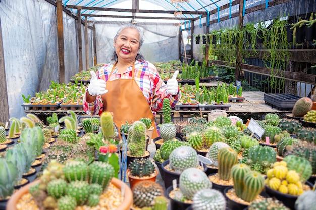 Anciana feliz con una granja de cactus