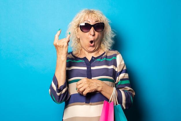 Anciana con gafas sostiene bolsas de la compra y muestra gesto de rock and roll en la pared azul.