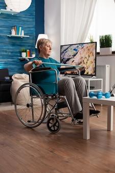 Anciana inválida en silla de ruedas estirando los músculos del cuerpo de entrenamiento de resistencia del brazo con banda elástica af ...