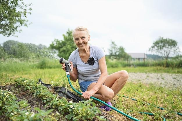 Anciana madura regar las plantas con una manguera de agua. concepto de agricultura, jardinería, agricultura, vejez y personas