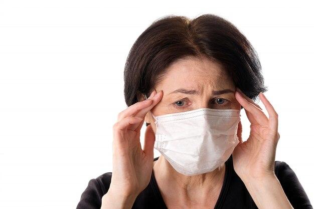 Una anciana en una máscara protectora médica, sosteniendo sus templos con dolor de cabeza, sobre una superficie blanca.
