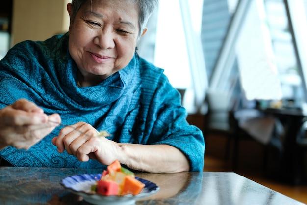 Anciana mayor asiática anciana comiendo fruta en el restaurante