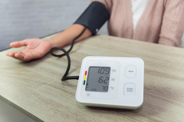 Anciana con medidor de presión comprobando el nivel de presión arterial en la mesa