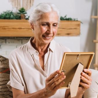 Una anciana mirando marco de fotos