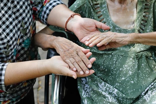 Anciana mujer asiática en silla de ruedas en casa con hija cuidando