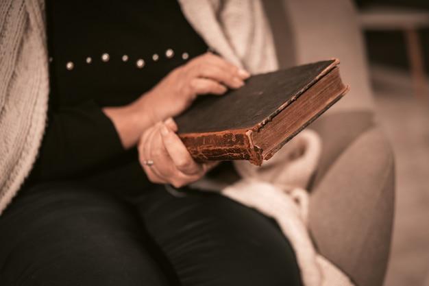 Anciana mujer de raza blanca tiene un libro antiguo en sus manos