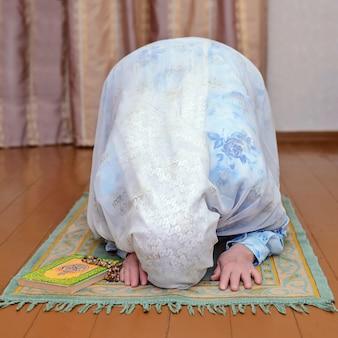 Anciana musulmana con un vestido azul brillante y un pañuelo blanco reza en la alfombra de oración verde