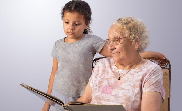 Anciana y niño leyendo un libro en gris