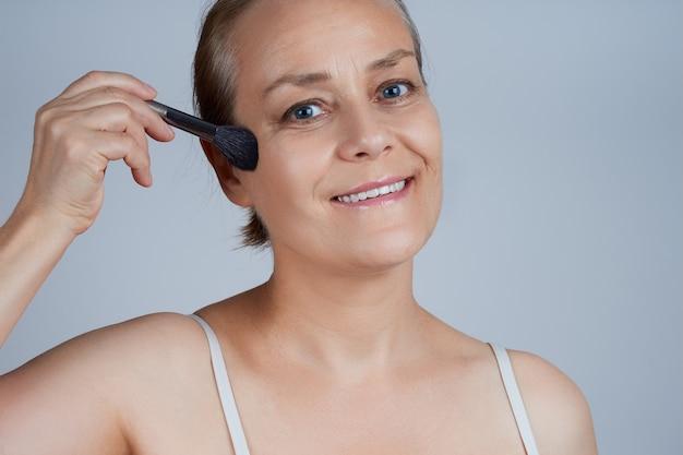 Una anciana se pone cosméticos decorativos en las mejillas. cuidado de la piel de la cara en la vejez.
