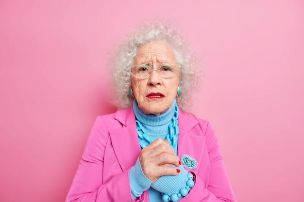 Anciana preocupada con la cara arrugada mantiene las manos juntas, parece decepcionada, se siente nerviosa por algo, usa gafas, ropa de moda