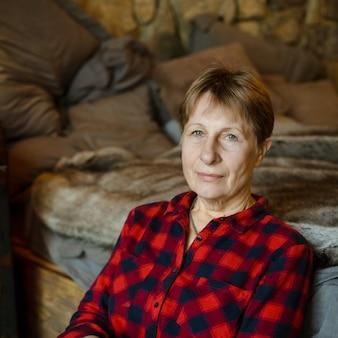 Anciana sentada al lado de la cama en el chalet. retrato.