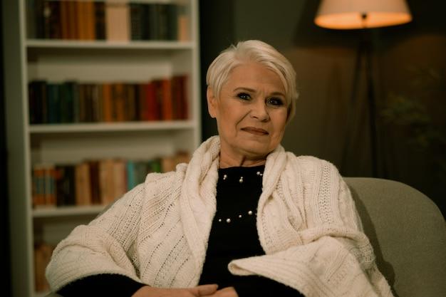 Anciana sentada en una silla en una habitación acogedora