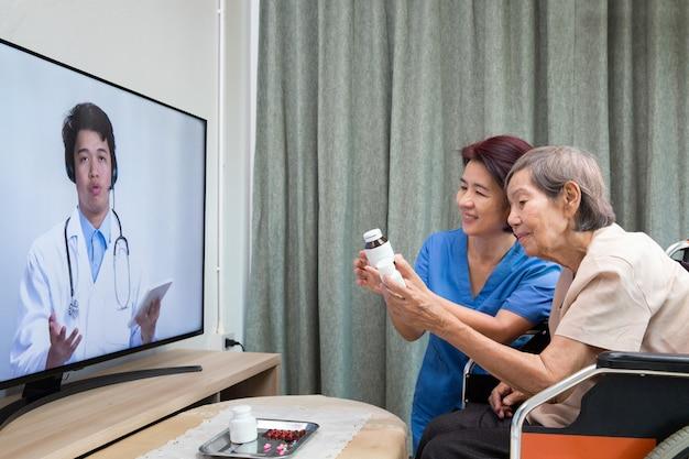Anciana sentarse en casa teniendo consulta en línea con el médico.