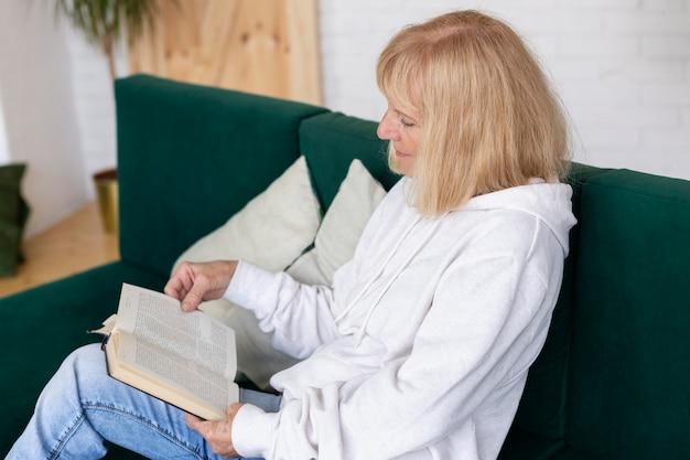 Anciana en el sofá en casa leyendo un libro
