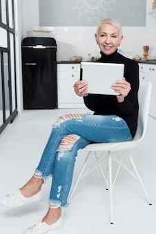 Anciana sonriendo y posando con tableta en la cocina