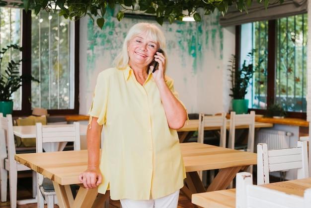 Anciana sonriente anciana sosteniendo smartphone cerca de la oreja