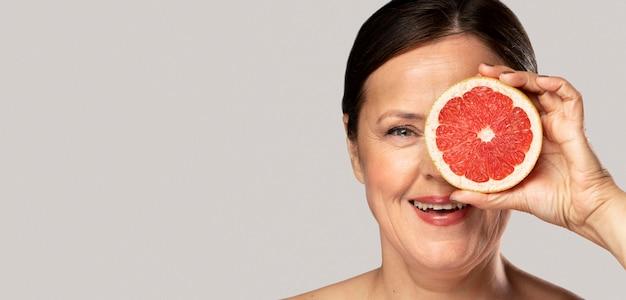 Anciana sonriente cubriendo su ojo con la mitad de pomelo