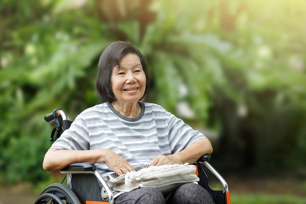 Anciana sonriente, sentada en silla de ruedas
