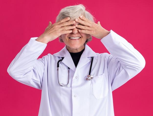 Anciana sonriente en uniforme médico con estetoscopio cubriendo los ojos con las manos
