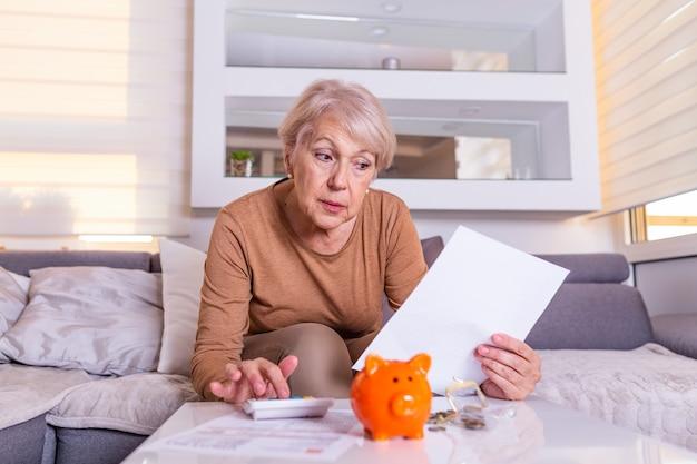 Una anciana sorprendida con las facturas que recibe, horrorizada y sin aliento. mujer senior comprobada las finanzas con calculadora en casa. mujer jubilada que calcula sus cuentas domésticas
