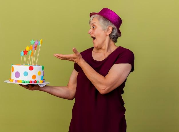 Anciana sorprendida con sombrero de fiesta sostiene y apunta a la torta de cumpleaños aislada en la pared verde oliva con espacio de copia