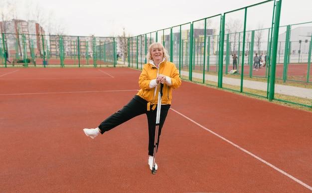 Una anciana sosteniendo un bastón nórdico se encuentra en el estadio en una cinta roja. estilo de vida saludable de las personas mayores