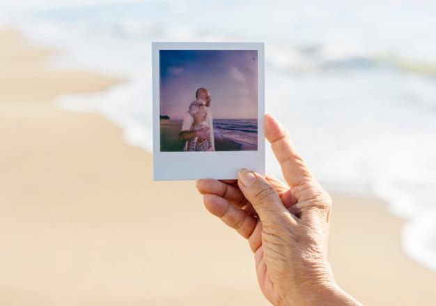 Anciana sosteniendo una fotografía en la playa