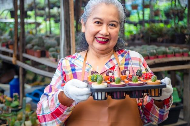 Anciana sosteniendo maceta de cactus con precio de venta