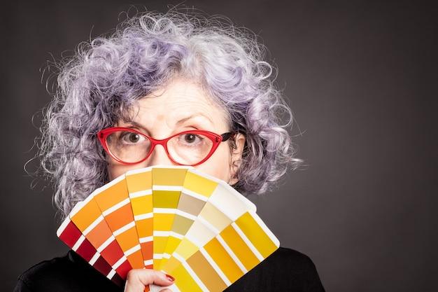 Anciana sosteniendo una paleta de colores sobre un fondo gris